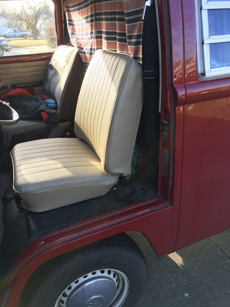 Newly reupholstered seat installed back in the van, looking at it from the side.