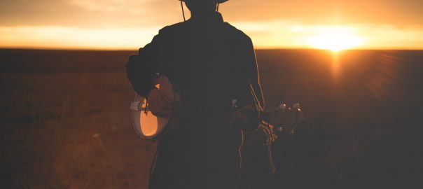 A banjo player standing in front of an orange tinged sunset